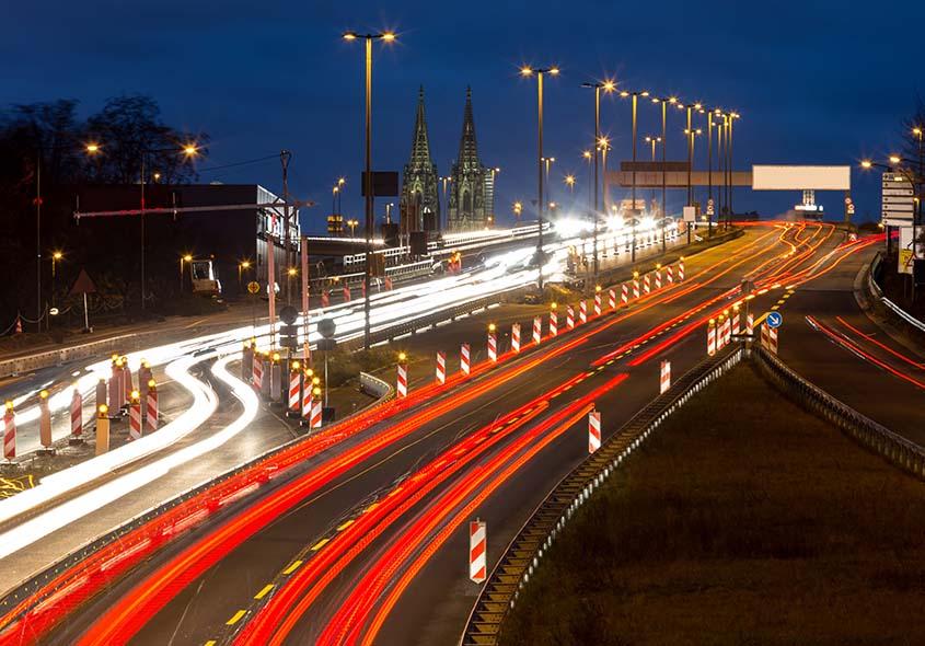 Bild von einer Brück in Köln mit Dom im Hintergrund bei Nacht